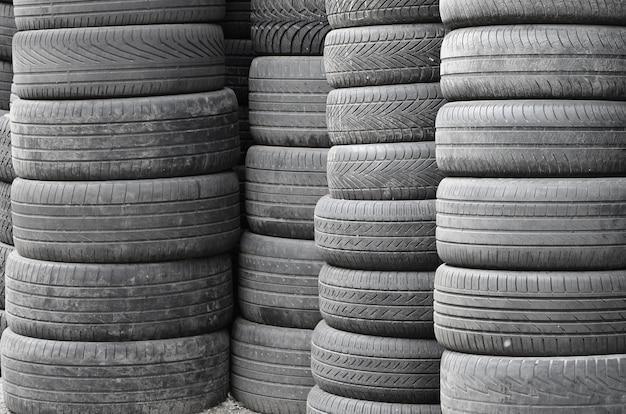 Oude gebruikte banden gestapeld met hoge stapels in de garage van de secundaire auto-onderdelenwinkel