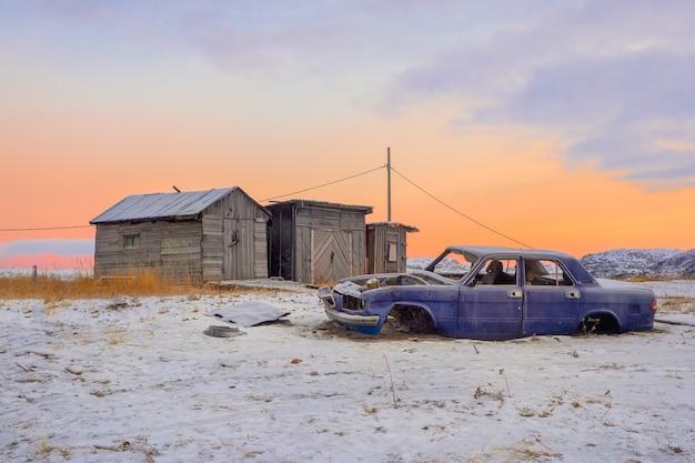 Oude gedemonteerde auto bij de garages in authentiek dorpje teriberka