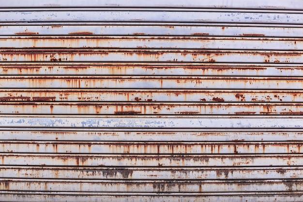 Oude gedetailleerde leeftijd van vintage roestige getextureerde zink legering metalen rol sluitertijd deur
