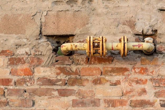 Oude gele gasleiding in een bakstenen muur. vreemd ontwerp.