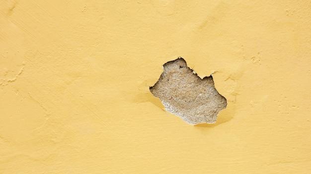 Oude gele gepelde pleistermuur