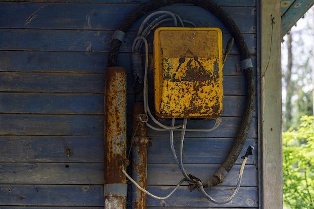 Oude gele roestige schakeldoos die op blauwe plankmuur van het huis hangt