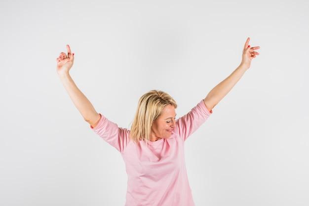 Oude gelukkige dame in roze blouse met upped handen