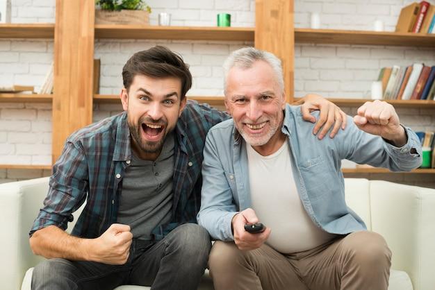 Oude gelukkige man met afstandsbediening en jonge huilende man tv kijken op de bank