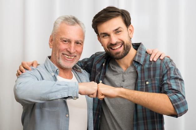Oude gelukkige mens die vuisten stoten en met jonge glimlachende kerel koesteren