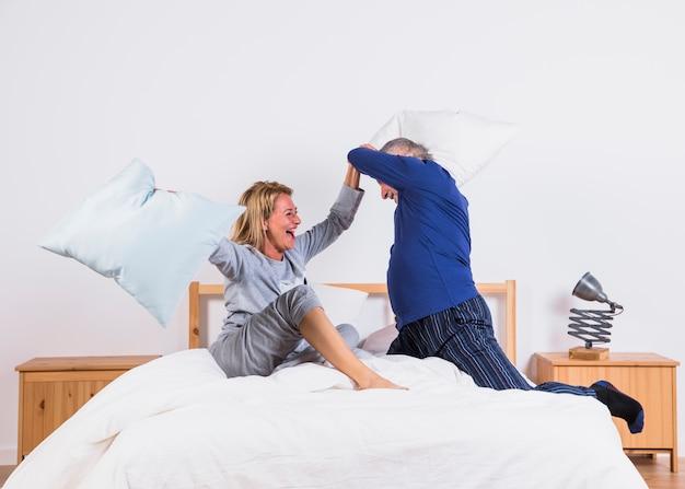 Oude gelukkige vrouw en man met hoofdkussens die pret op bed in slaapkamer hebben
