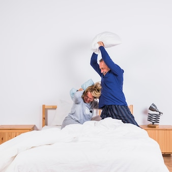Oude gelukkige vrouw en man met kussens plezier op bed