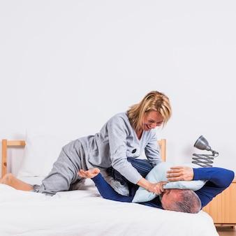Oude gelukkige vrouw en man met plezier met kussens op bed in de slaapkamer