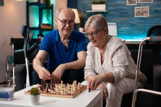 Oude gepensioneerde man en vrouw genieten van schaakspel