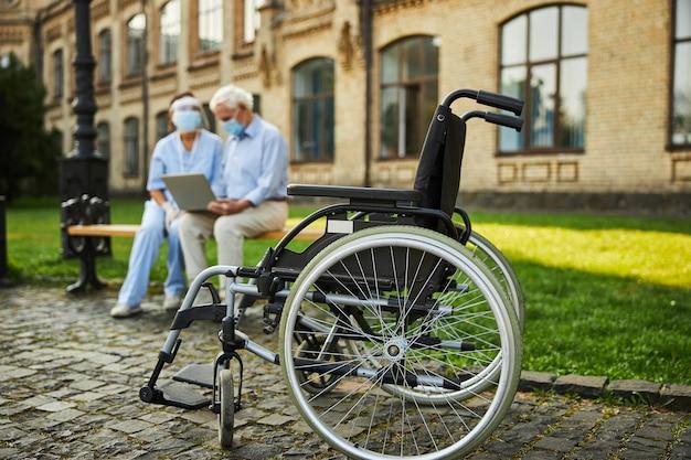 Oude gepensioneerde man zit in de buurt van verpleegster op bankje buiten