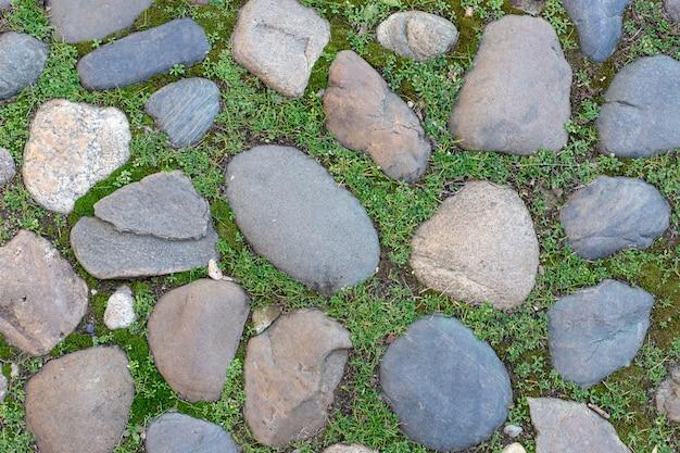 Oude geplaveide weg met gras en mos tussen de achtergrond van de steenentextuur