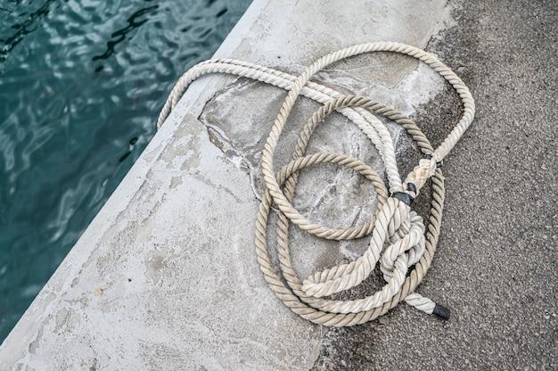 Oude geroeste meertrosmeerpaal met geknoopte zeevaartkabels. los gigantes, tenerife