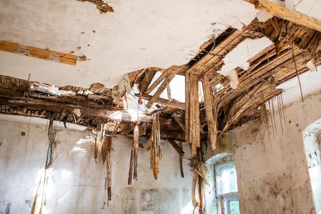 Oude geruïneerde latten op gebroken plafonddak van een verlaten huis.