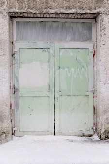Oude geschilderde groene gesloten deur. vooraanzicht. verticaal.