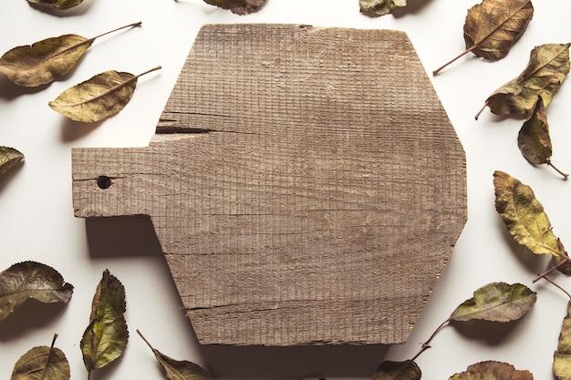 Oude gesneden bord met droge bladeren op een witte achtergrond.