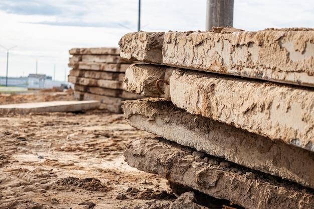 Oude gewapend betonnen wegplaten gestapeld op een bouwplaats voor later gebruik. tijdelijk wegdek.