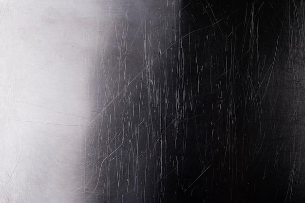 Oude glanzende metalen achtergrond, donkere geborsteld metalen textuur met krassen en licht verloop