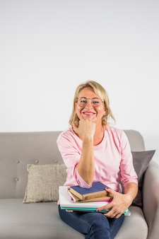 Oude glimlachende vrouw in roze blouse en oogglazen met hoop van boeken op bank