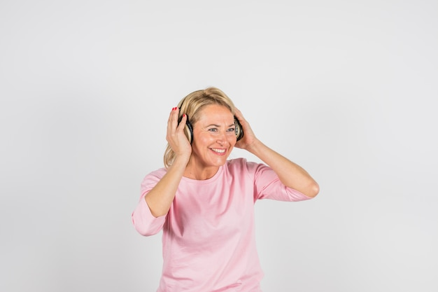 Oude glimlachende vrouw in roze blouse met hoofdtelefoons