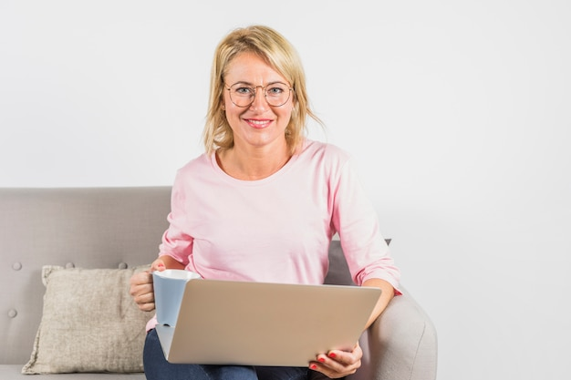 Oude glimlachende vrouw in roze blouse met laptop en kop op bank
