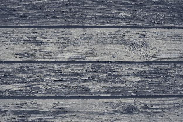 Oude grijze armoedige houten planken met gebarsten kleur verf