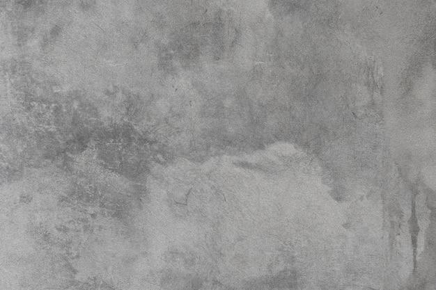 Oude grijze betonnen cementmuur met witte vlekken en kleine scheuren in de textuur.