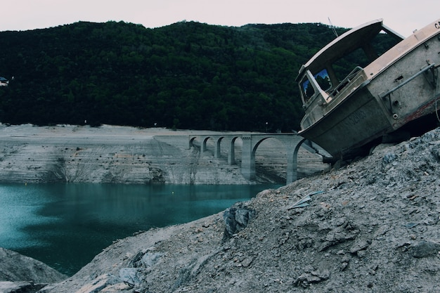 Oude grijze boot op een rotsachtige oppervlakte dichtbij een boogbrug op het water dat door bomen wordt omringd