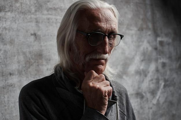 Oude grijze haren blanke gepensioneerde man na te denken over het leven. grootvader in glazen met snor en doordachte gelaatsuitdrukking houdt zijn kin vast