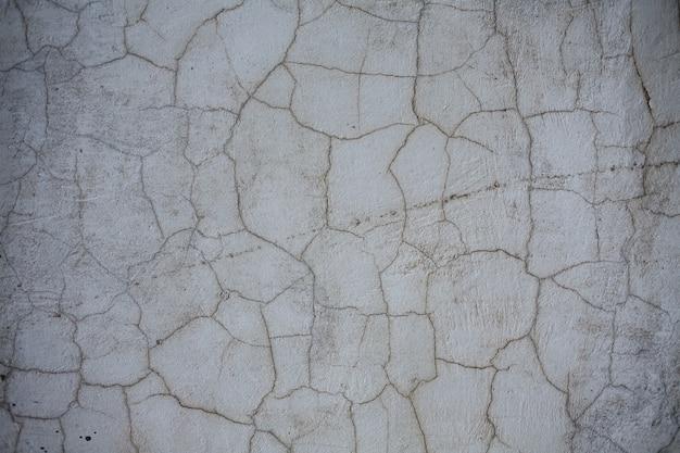 Oude grijze straatmuurachtergrond, textuur met barsten en krassen