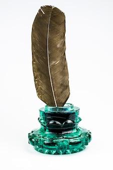 Oude groene glazen inktpotje en een grote donkere ganzenveer geïsoleerd op een witte achtergrond.