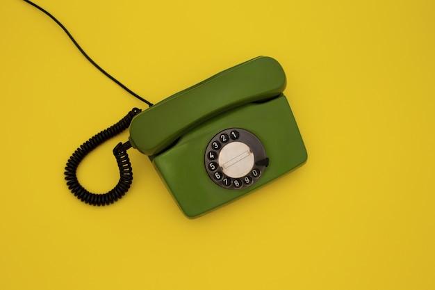 Oude groene wijzerplaattelefoon op geel
