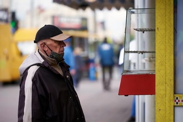 Oude grootvader, gekleed in een medisch masker, met een pet op, kijkt naar een lege toonbank