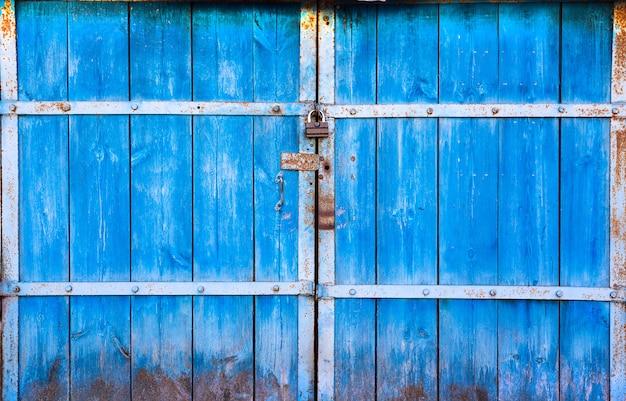 Oude grote houten deuren geschilderd in blauw en gesloten op het hangslot