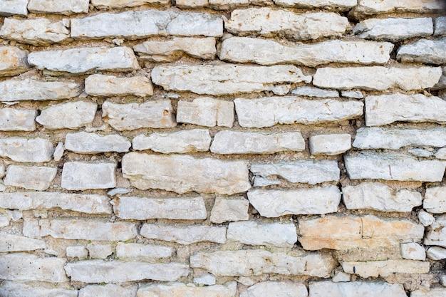 Oude grunge bakstenen muur muur. fragment van een oude stenen muur. detail van oude witte bakstenen muur, textuur.