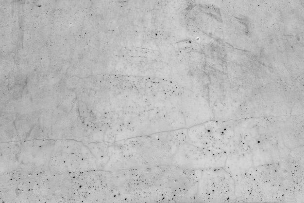 Oude grunge grijze muur met kleine gaten.