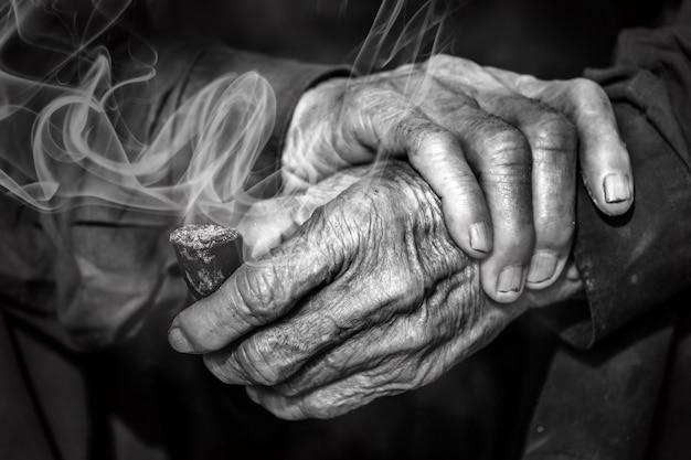 Oude handen die de pijp met rook houden