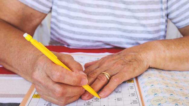 Oude handen doen een kruiswoordpuzzel