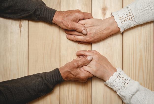 Oude handen van een bejaarde echtpaar samen, hand in hand