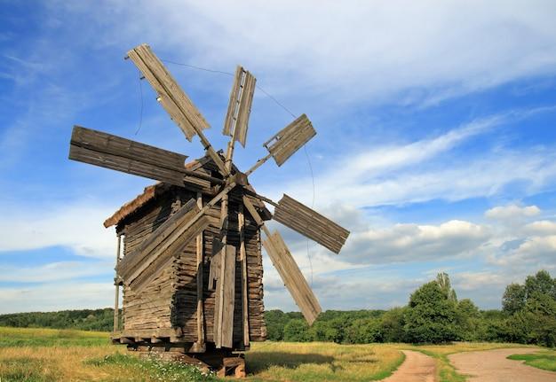 Oude historische verouderde windmolen dichtbij landweg in gebied