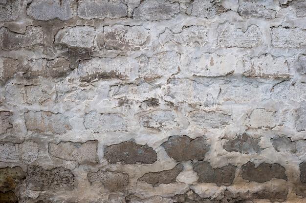 Oude hobbelige bakstenen muur geschilderd in witte kleur