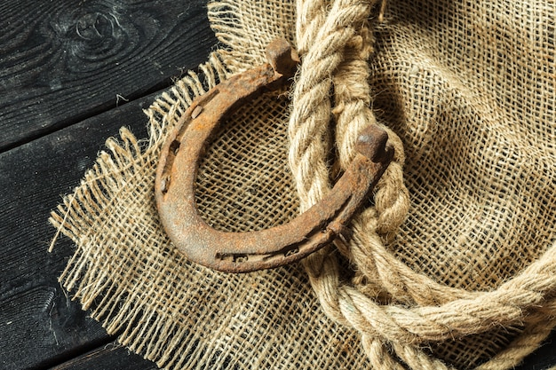 Oude hoefijzer en touw op houten planken