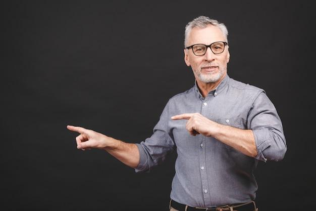Oude hogere mens die glazen dragen die tegen zwarte verbaasde achtergrond worden geïsoleerd en glimlachen terwijl het voorstellen met hand en het richten met vinger.