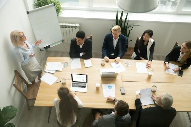 Oude hogere onderneemster die presentatie geeft op multiraciale groepsbureauvergadering