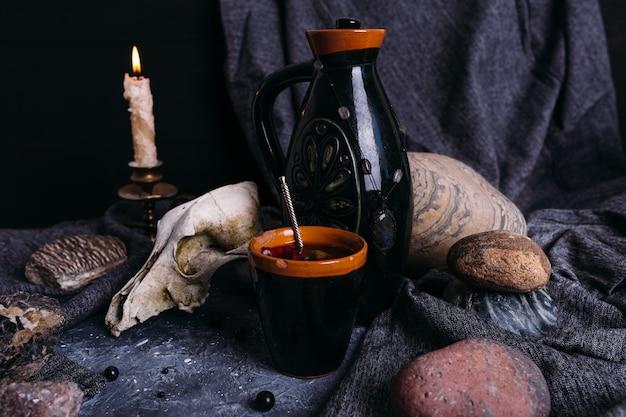 Oude hondenschedelkruik en stenen op heksentafel betoverde drank met bloemblaadjes