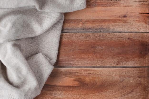 Oude houten achtergrond en gebreide warme trui. herfst decoratie en vrije ruimte voor tekst. bovenaanzicht. ruimte kopiëren