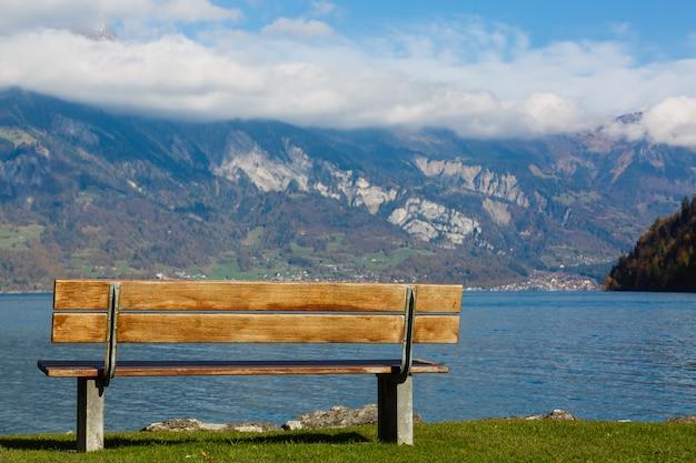 Oude houten bank in de buurt van de kust van een bergmeer.