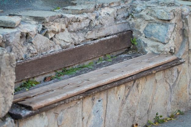 Oude houten bankje in de stenen muur