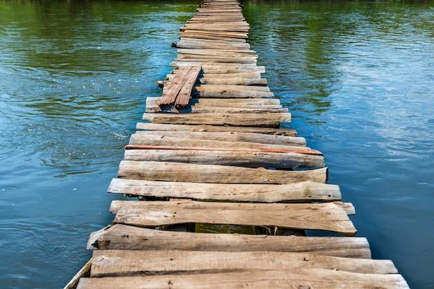 Oude houten brug door de rivier met groene bomen aan de oevers