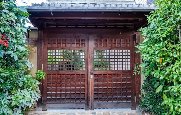 Oude houten deur gesloten met groene flora schaduwrijke tuin