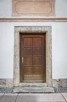 Oude houten deur in de witte bouw in europa